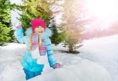 Το μικρό κορίτσι ρίχνει τη χιονιά στο πάρκο Στοκ Εικόνα