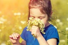 Το μικρό κορίτσι ρουθουνίζει τα λουλούδια Στοκ Εικόνες