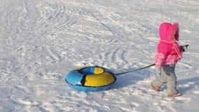 Το μικρό κορίτσι σέρνει το φωτεινό snowtube στο χιόνι απόθεμα βίντεο