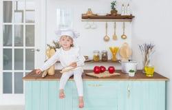 Το μικρό κορίτσι σε έναν μάγειρα ΚΑΠ με έναν μορφασμό σε ένα πρόσωπο κάθεται στον πίνακα με τα μήλα Στοκ Εικόνες