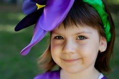 Το μικρό κορίτσι σε ένα κοστούμι του ιώδους λουλουδιού χαμογελά στην ΤΣΕ Στοκ φωτογραφία με δικαίωμα ελεύθερης χρήσης