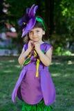Το μικρό κορίτσι σε ένα κοστούμι του ιώδους λουλουδιού χαμογελά Στοκ φωτογραφία με δικαίωμα ελεύθερης χρήσης