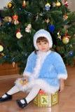 Το μικρό κορίτσι σε ένα κοστούμι του κοριτσιού χιονιού κάθεται για ένα νέο δέντρο έτους στοκ εικόνα