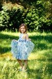 Το μικρό κορίτσι σε ένα μπλε φόρεμα παραδίδει μέσα το θερινό κήπο Στοκ Φωτογραφίες