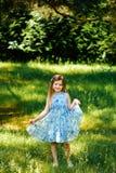 Το μικρό κορίτσι σε ένα μπλε φόρεμα παραδίδει μέσα το θερινό κήπο Στοκ φωτογραφία με δικαίωμα ελεύθερης χρήσης