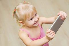 Το μικρό κορίτσι σε ένα ρόδινο φόρεμα κοιτάζει επίμονα στο τηλέφωνο Στοκ εικόνες με δικαίωμα ελεύθερης χρήσης