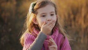 Το μικρό κορίτσι σε ένα φως ηλιοβασιλέματος φυσά ένα φιλί στη κάμερα απόθεμα βίντεο