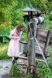 Το μικρό κορίτσι σε ένα φόρεμα κοιτάζει στο φρεάτιο Στοκ φωτογραφία με δικαίωμα ελεύθερης χρήσης