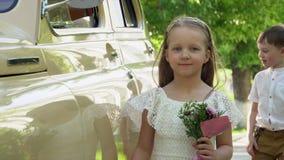 Το μικρό κορίτσι σε ένα όμορφο ελαφρύ φόρεμα με μια μικρή ανθοδέσμη των δαπανών λουλουδιών στο αναδρομικό αυτοκίνητο του μπεζ χρώ φιλμ μικρού μήκους