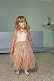 Το μικρό κορίτσι σε ένα όμορφο φόρεμα παίζει στο σπίτι στοκ φωτογραφία
