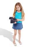 Το μικρό κορίτσι στέκεται και κοιτάζει επάνω στη μάσκα Στοκ Εικόνα