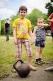 Το μικρό κορίτσι στέκεται κοντά σε ένα kettlebell στους ερασιτεχνικούς ανταγωνισμούς στοκ εικόνες