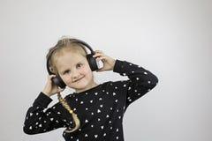 Το μικρό κορίτσι στα μεγάλα ακουστικά χαμογελά και εξετάζει τη κάμερα στοκ εικόνες με δικαίωμα ελεύθερης χρήσης