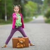 Το μικρό κορίτσι στα φωτεινά ενδύματα που στέκονται στο δρόμο με μια βαλίτσα και ένα Teddy αντέχουν Ταξίδι Στοκ Εικόνα