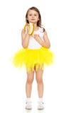 Το μικρό κορίτσι στην κίτρινη φούστα που τρώει μια μπανάνα Στοκ Φωτογραφία