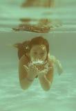 Το μικρό κορίτσι στην κολύμβηση λιμνών ξενοδοχείων υποβρύχια και το smilin στοκ εικόνες με δικαίωμα ελεύθερης χρήσης
