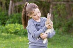 Το μικρό κορίτσι στην οδό για να κρατήσει ένα ζωντανό κουνέλι Στοκ Εικόνες