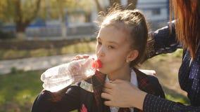 Το μικρό κορίτσι στη σχολική στολή πίνει το νερό από ένα πλαστικό μπουκάλι Η μητέρα ρυθμίζει το δεσμό κορών της, και το κορίτσι α απόθεμα βίντεο