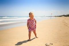Το μικρό κορίτσι στις διάστικτες στάσεις εξετάζει το γάντι από την κυματωγή κυμάτων Στοκ Εικόνες