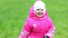 Το μικρό κορίτσι στις θερμές στάσεις ενδυμάτων στη χλόη, χαμογελά και γελά φιλμ μικρού μήκους