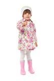 Το μικρό κορίτσι στις μπότες και ένα σακάκι εμφανίζει δάχτυλο Στοκ Φωτογραφία