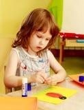 Το μικρό κορίτσι στον πίνακα που κολλά τις εφαρμογές Στοκ εικόνα με δικαίωμα ελεύθερης χρήσης