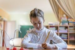 το μικρό κορίτσι στο γραφείο γράφει στοκ εικόνα με δικαίωμα ελεύθερης χρήσης