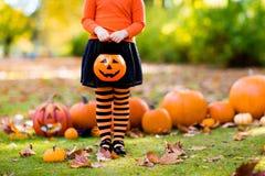 Το μικρό κορίτσι στο κοστούμι μαγισσών στο τέχνασμα αποκριών ή μεταχειρίζεται Στοκ Φωτογραφία