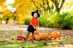 Το μικρό κορίτσι στο κοστούμι μαγισσών στο τέχνασμα αποκριών ή μεταχειρίζεται Στοκ εικόνα με δικαίωμα ελεύθερης χρήσης