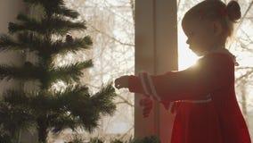 Το μικρό κορίτσι στο κόκκινο φόρεμα που διακοσμεί το χριστουγεννιάτικο δέντρο με ένα μελόψωμο φιλμ μικρού μήκους