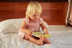 το μικρό κορίτσι στο ροζ κάθεται στον καναπέ και εξετάζει την κάλυψη βιβλίων Στοκ φωτογραφία με δικαίωμα ελεύθερης χρήσης