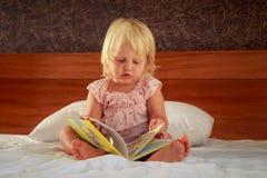 το μικρό κορίτσι στο ροζ κάθεται στον καναπέ και εξετάζει την κάλυψη βιβλίων Στοκ Εικόνα