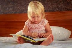 το μικρό κορίτσι στο ροζ κάθεται στον καναπέ και εξετάζει την κάλυψη βιβλίων Στοκ φωτογραφίες με δικαίωμα ελεύθερης χρήσης