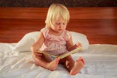 το μικρό κορίτσι στο ροζ κάθεται στον καναπέ και εξετάζει την κάλυψη βιβλίων Στοκ εικόνες με δικαίωμα ελεύθερης χρήσης