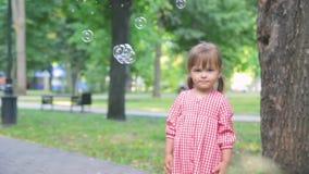 Το μικρό κορίτσι στο ρόδινο φόρεμα πιάνει τις φυσαλίδες σαπουνιών, σε αργή κίνηση φιλμ μικρού μήκους