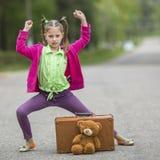 Το μικρό κορίτσι στο δρόμο με μια βαλίτσα και ένα Teddy αντέχουν Στοκ Φωτογραφίες