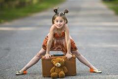 Το μικρό κορίτσι στο δρόμο με μια βαλίτσα και ένα Teddy αντέχουν Στοκ εικόνες με δικαίωμα ελεύθερης χρήσης
