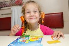 Το μικρό κορίτσι στο τραίνο με μια ευτυχή συνεδρίαση χαμόγελου σε έναν πίνακα στο χαμηλότερο δεύτερης θέσης αυτοκίνητο θέσεων και Στοκ Φωτογραφία