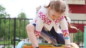 Το μικρό κορίτσι στο φόρεμα αναρριχείται στην παιδική χαρά παιδιών στη θερινή ημέρα απόθεμα βίντεο