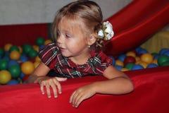 το μικρό κορίτσι στο φόρεμα καρό κυλά κάτω ένα children& x27 φωτογραφική διαφάνεια του s στο α στοκ εικόνες