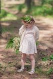 Το μικρό κορίτσι στο φόρεμα στέκεται σε ένα δάσος πεύκων και κρατά την ανθοδέσμη των wildflowers Στοκ Εικόνες
