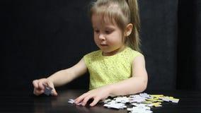Το μικρό κορίτσι συλλέγει τους γρίφους στον πίνακα σε ένα σκούρο γκρι υπόβαθρο φιλμ μικρού μήκους