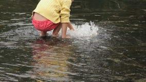 Το μικρό κορίτσι συλλέγει χωρίς παπούτσια τα νομίσματα στην πηγή φιλμ μικρού μήκους