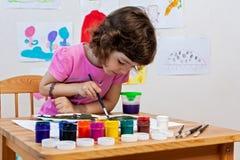 Το μικρό κορίτσι σύρει με τα χρώματα και το πινέλο Στοκ Φωτογραφίες