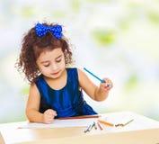 Το μικρό κορίτσι σύρει στον πίνακα με τα μολύβια Στοκ εικόνα με δικαίωμα ελεύθερης χρήσης
