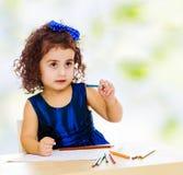 Το μικρό κορίτσι σύρει στον πίνακα με τα μολύβια Στοκ Φωτογραφία