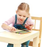 Το μικρό κορίτσι σύρει τα μολύβια καθμένος στον πίνακα Στοκ Φωτογραφίες