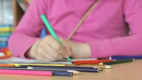 Το μικρό κορίτσι σύρει τις εικόνες στο copybook φιλμ μικρού μήκους