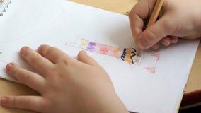 Το μικρό κορίτσι σύρει τις εικόνες στο copybook απόθεμα βίντεο