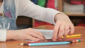 Το μικρό κορίτσι σύρει τις εικόνες χρησιμοποιώντας τα μολύβια χρώματος απόθεμα βίντεο